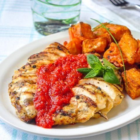 Lemon Herb Grilled Chicken with Spicy Roasted Red Pepper Sauce shown with roasted sweet potatoes on a white plate.