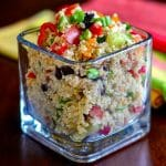 Mediterranean Quinoa Salad in a clear glass serving dish on a wooden table