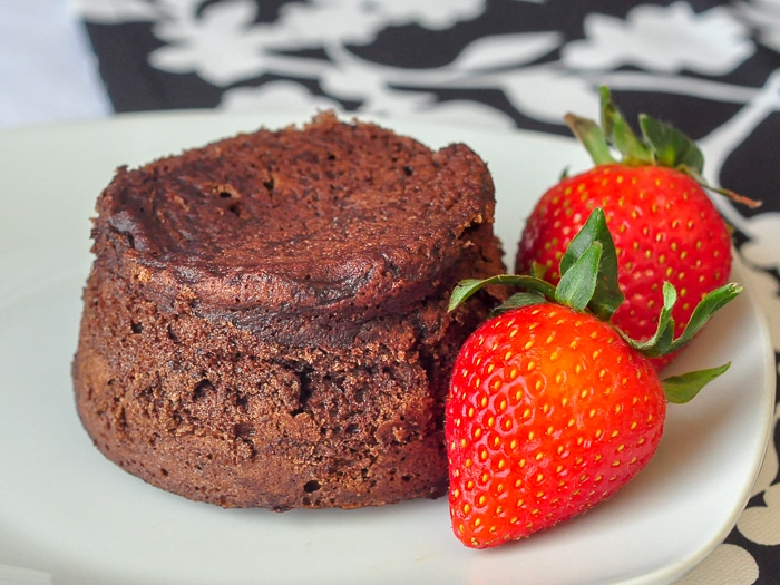 Molten Chocolate Mousse Cake with strawberries on a white plate