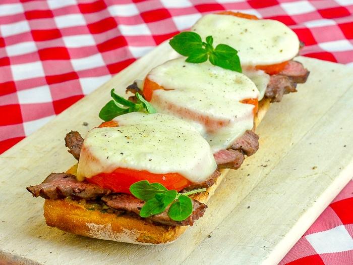 Open Face Tomato Provolone Steak Sandwich wide shot photo odf full sandwich on a wooden cuting board