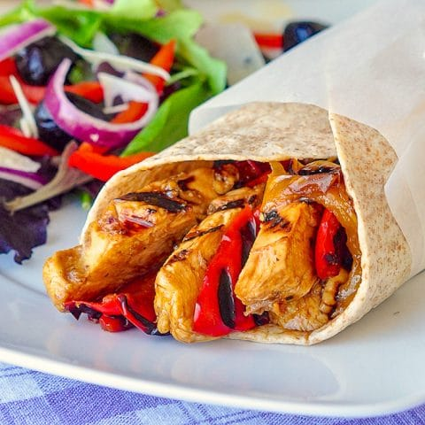 Orange Balsamic Chicken Wraps close up image on white plate with salad on the side