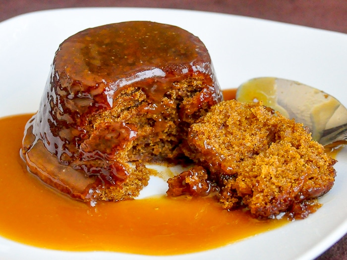 Perfect Sticky Toffee Pudding wide shot photo of singoe serving on a white plate