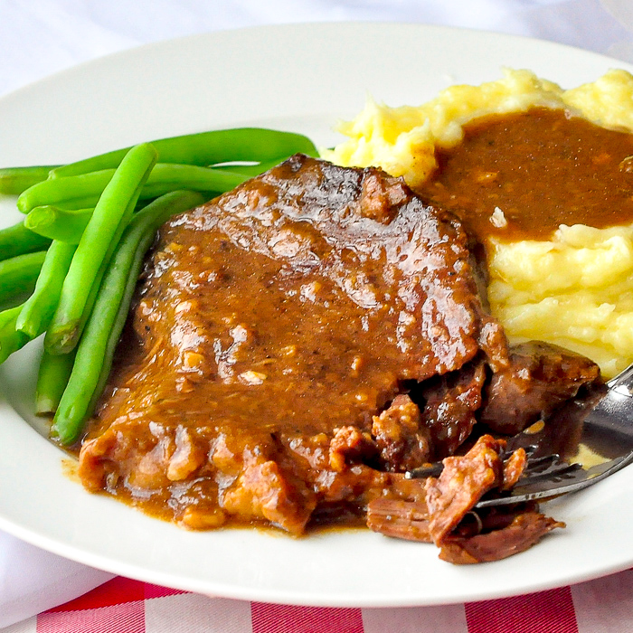 Photo of one serving of stewed steak shown with mashed potatoes and green beans