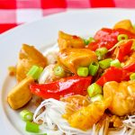 Spicy Stir Fried Orange Chicken close up photo of single serving on white plate