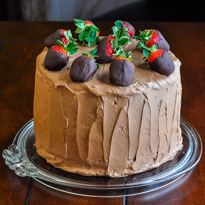 Too Tall Neapolitan Cake photo of entire uncut cake topped with a ring of chocolate dipped strawberries