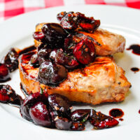 Two Grilled Pork Chops with Balsamic Thyme Cherries on a white plate