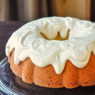 Vanilla Cream Cheese Bundt Cake photo of uncut cake on a clear glass serving plate