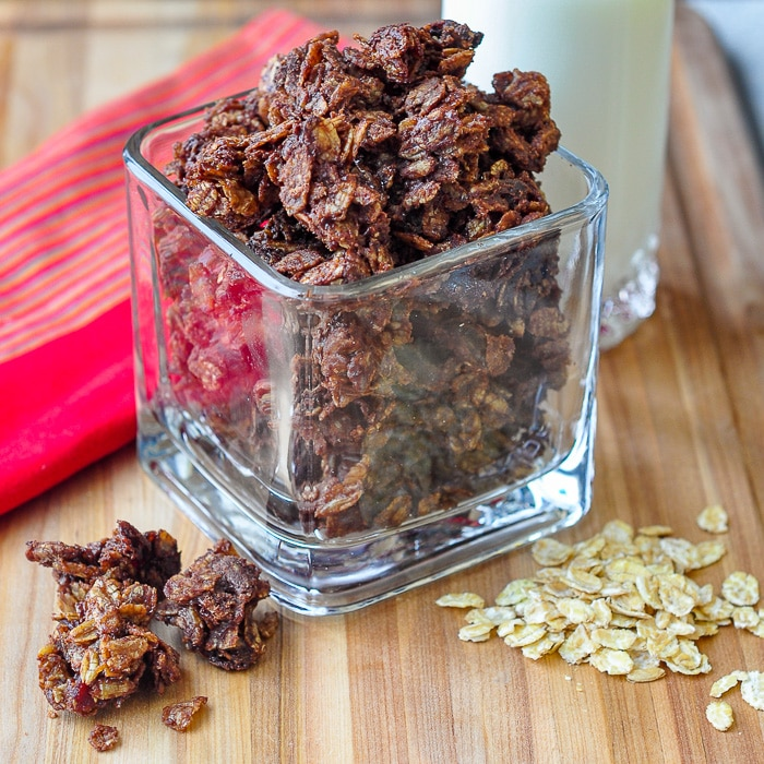 Chocolate Kamut Granola in a clear glass container on a wooden cutting board
