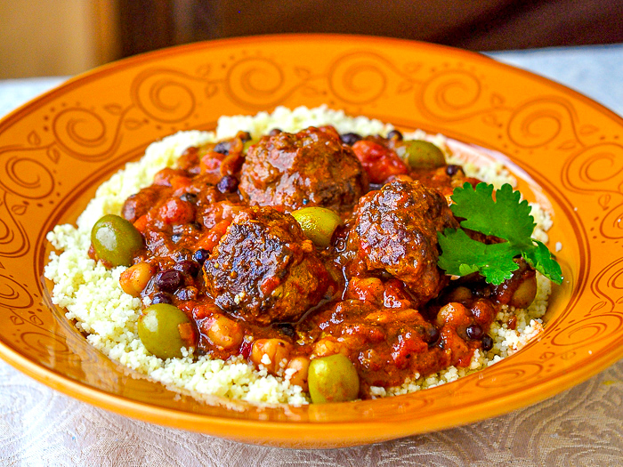 photo of Moroccan Meatball Stew in an orange patterned bowl with couscous