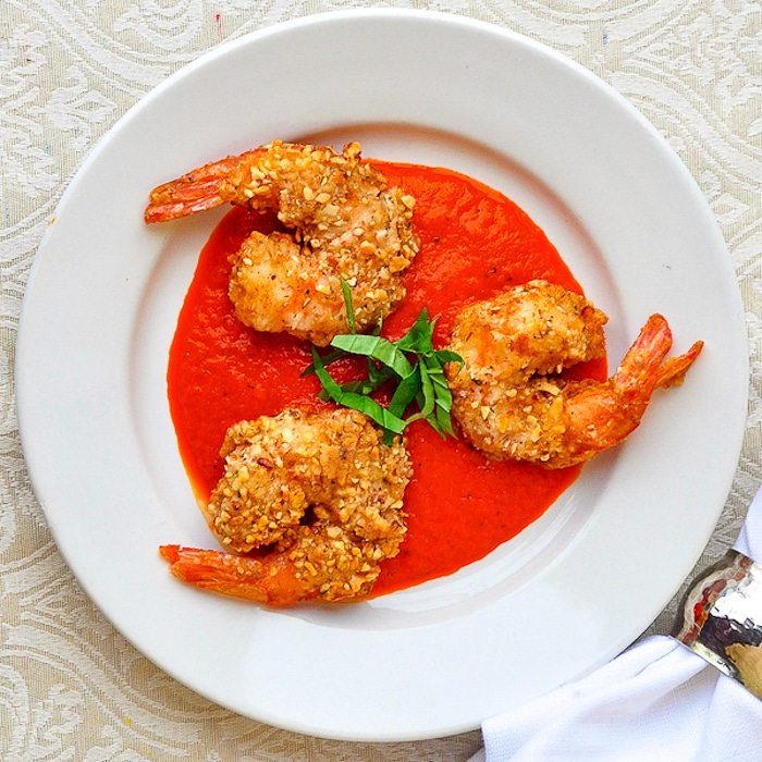 Almond Crusted Shrimp with Roasted Red Pepper Sauce pictured on a white plate with chopped basil garnish