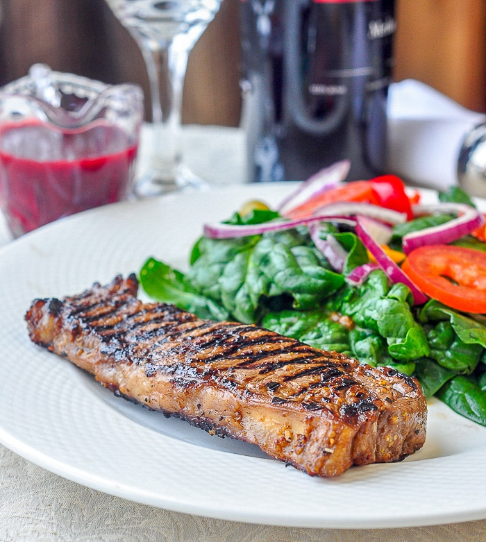 Dijon Balsamic Marinated Steak shown on a white plate with salad