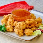 Double Crunch Popcorn Shrimp with Chili Lime Dipping Sauce shown on serving platter with dip in the centre