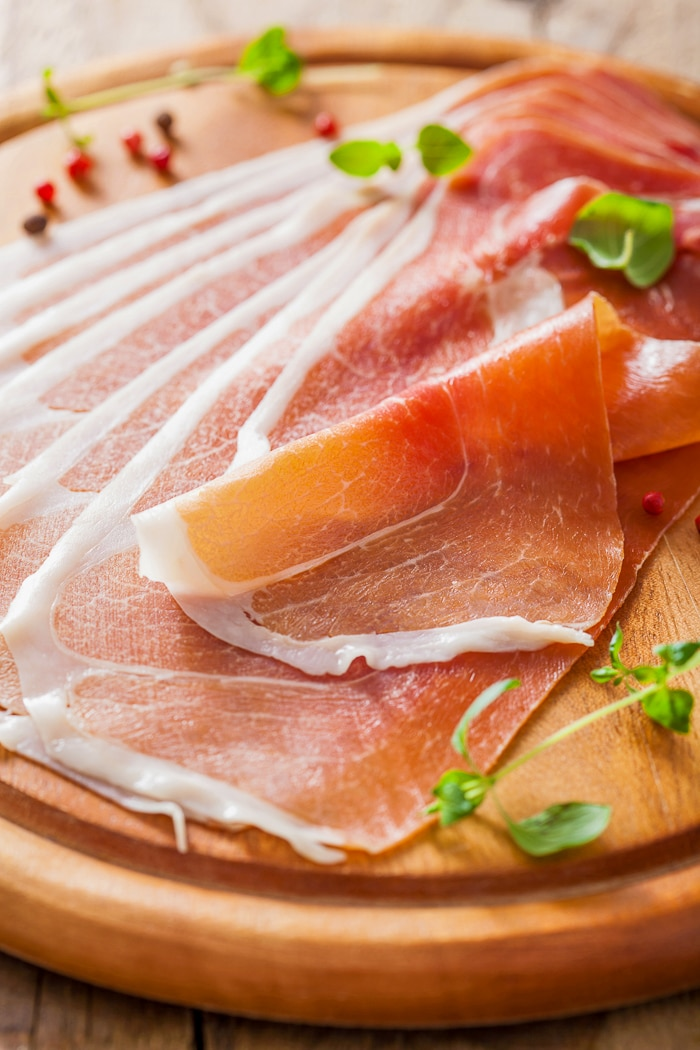 Thinly sliced prosciutto ham on chopping board