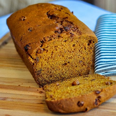 Pumpkin Bread with first slice cut, shown on wooden cutting board.