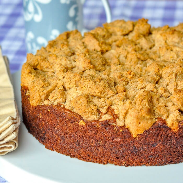 Walnut Crumble Banana Coffee Cake photo of uncut cake on white serving plate