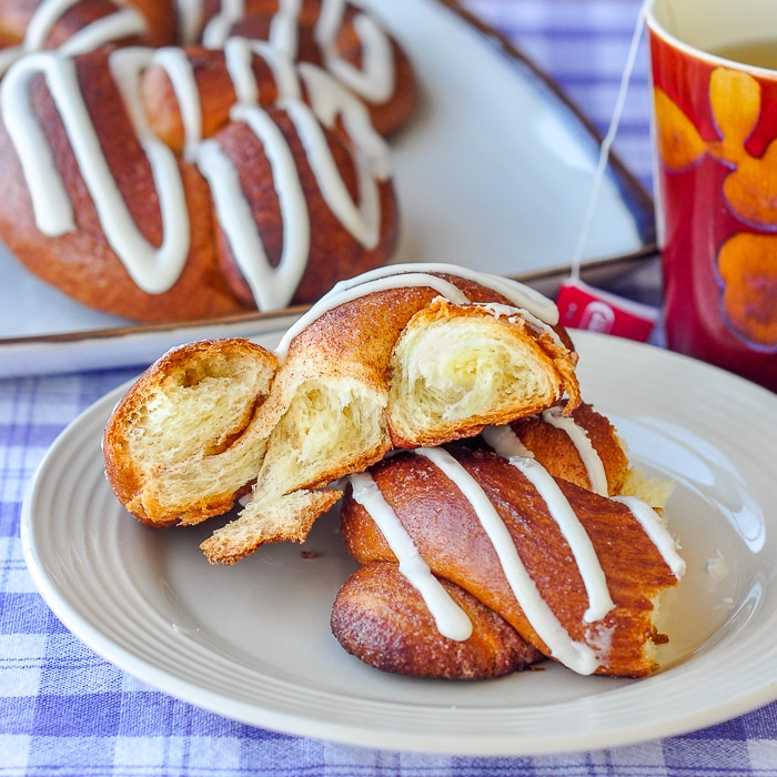 Brioche Cinnamon Knots photo of one roll torn open on plate to reveal the buttery texture