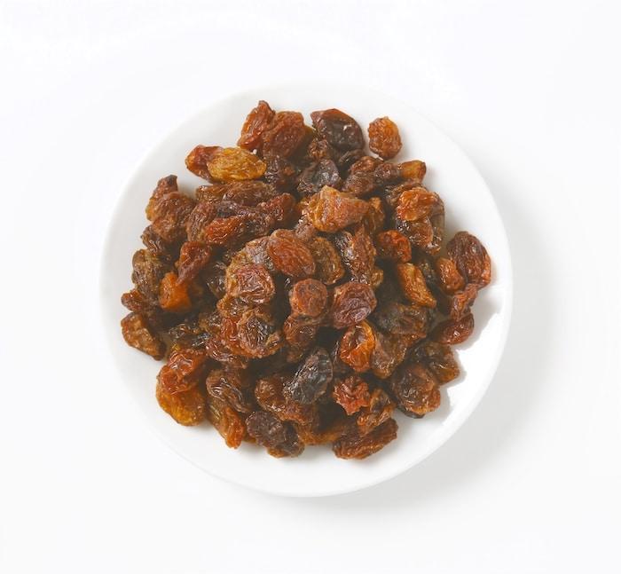 Raisins for Hot Cross Buns shown in a white bowl.