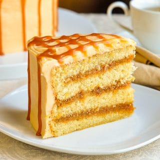 The Best Caramel Cake slice of cake on a white plate with coffee in background