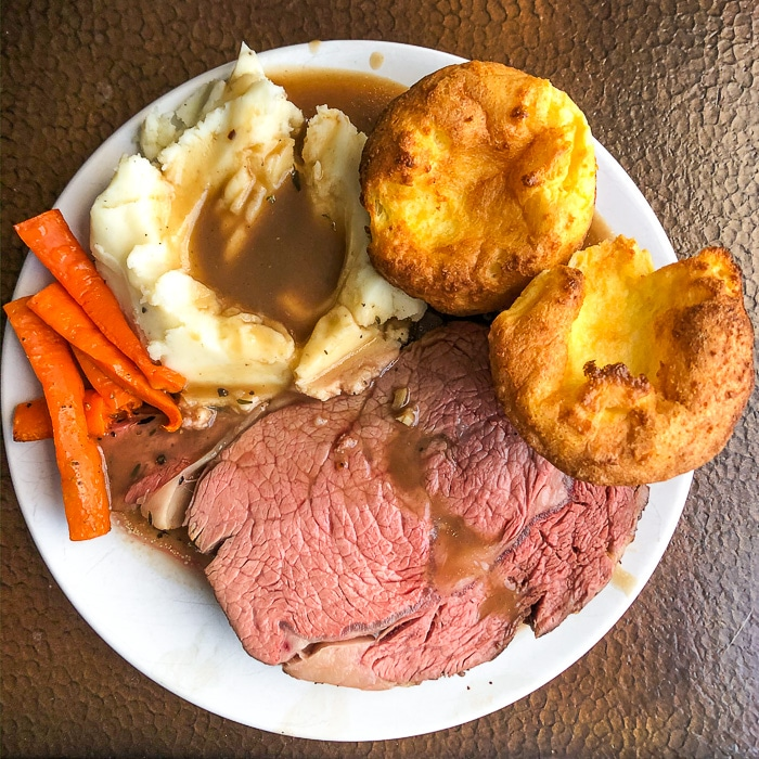 Herb and Garlic Crusted Prime Rib Roast plated with mashed potatoes, gravy, roasted carrots and yorkshire pudding.