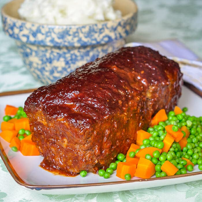 Old Fashioned Meatloaf with sweet onion glaze shown on seving platter with peas and carrots.