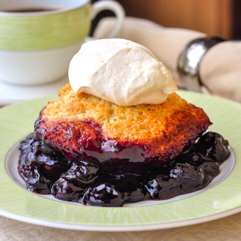 Photo of a single serving of cherry cobbler on a green and white plate