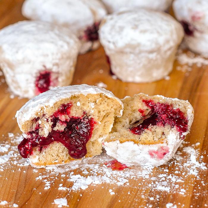 Raspberry Filled Donut Muffins shown on a dark brown wooden cutting board