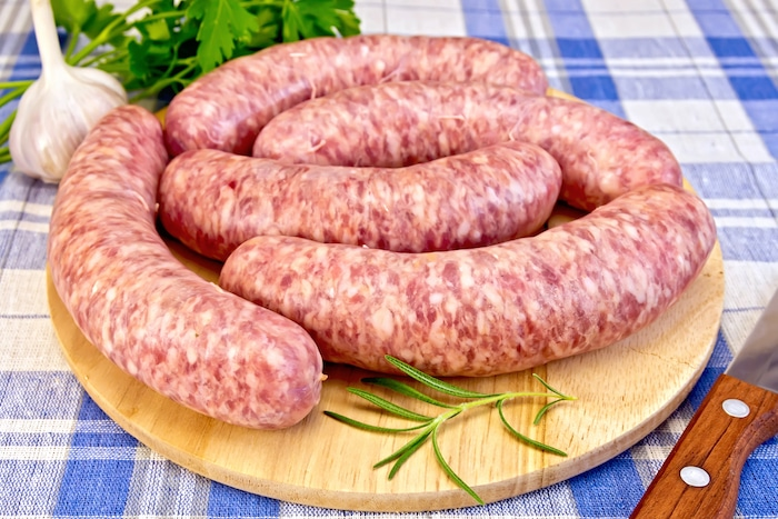 Raw pork sausages on a round wooden board, knife, rosemary, parsley and garlic on blue background checkered cloth