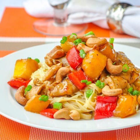Spicy Mango Orange Pork with Cashews close up of a single serving on a white plate