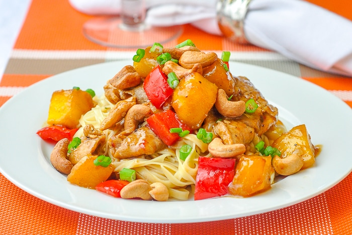 Spicy Mango Orange Pork with Cashews wide shot of a single serving on a white plate