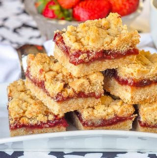 Strawberry Crumble close up photo of stacked cookie bars on a white plate