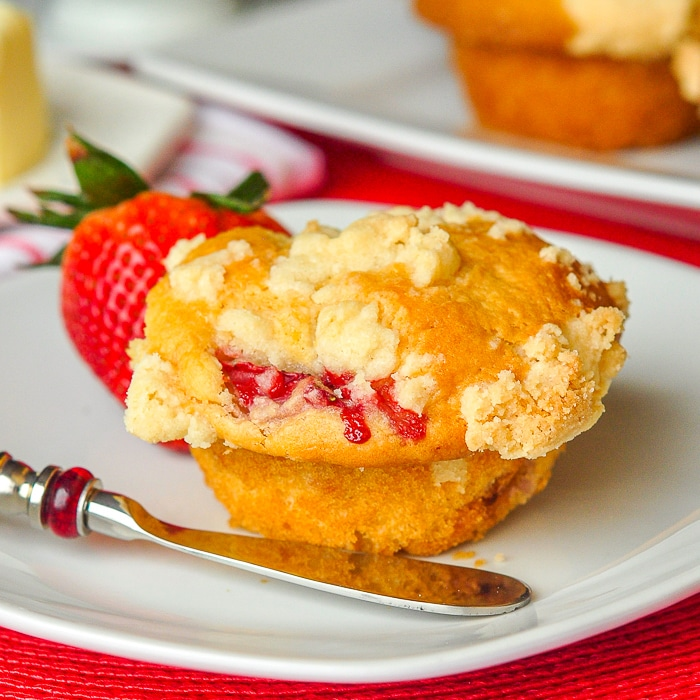 Strawberry Muffins with Shortbread Crumble close up photo of a single muffin on a white plate