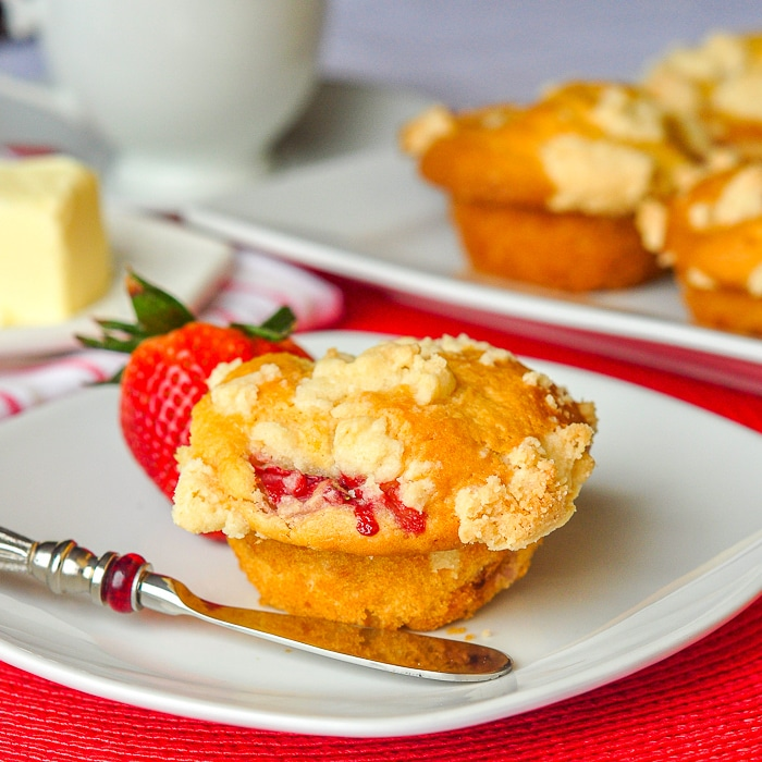 Strawberry Muffins with Shortbread Crumble photo of a single muffin with coffee and more muffins in the background