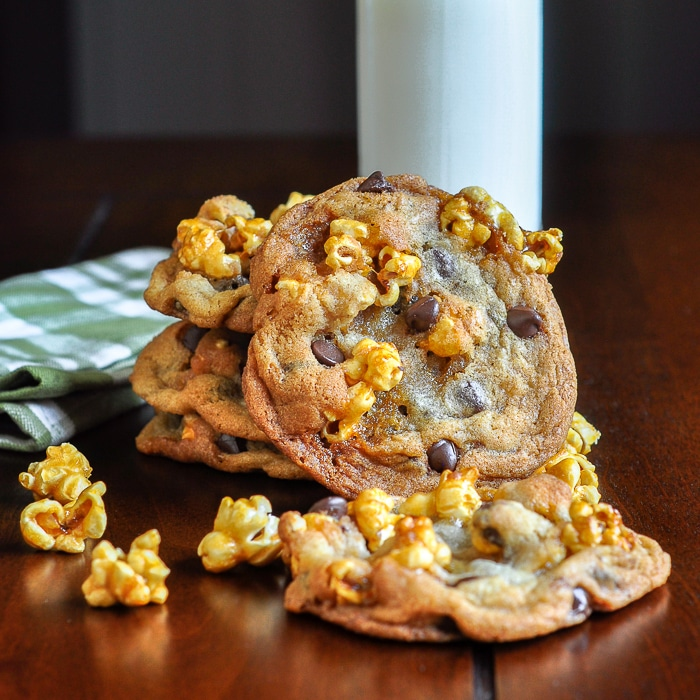 Caramel Corn Chocolate Chip Cookies on a wooden table with a glass of milk and napkin
