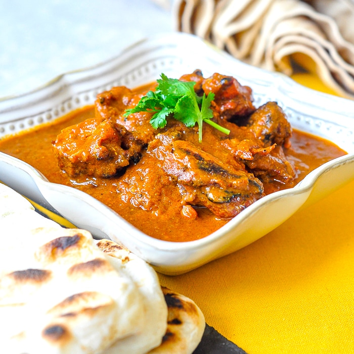 Low Fat Tomato Tandoori Chicken Curry. in white bowl with naan bread on the side