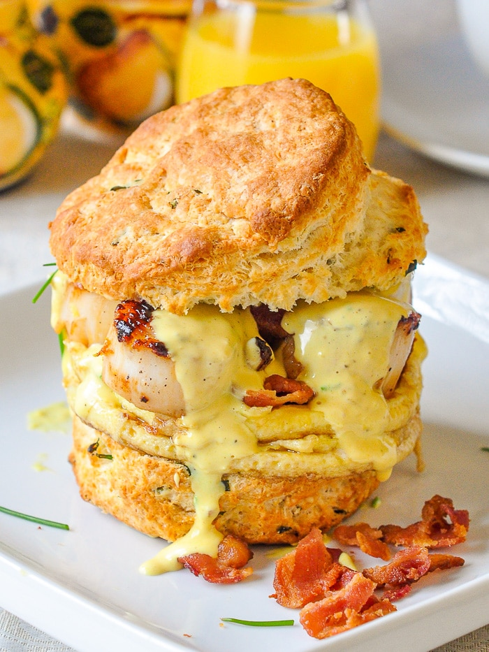 Scallops Benedict shown as a sandwich with the top jalf of the biscuit added on top
