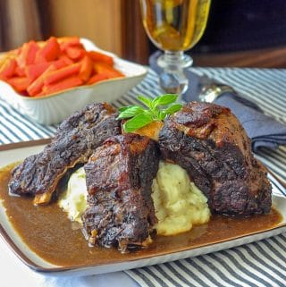 St. John's Stout Braised Beef Ribs on brown rimmed plate with gravy and mashed potatoes.
