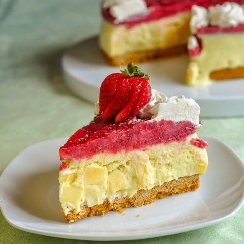 Strawberry Mango Ice Cream Pie vertical photo of single slice with pie in background.