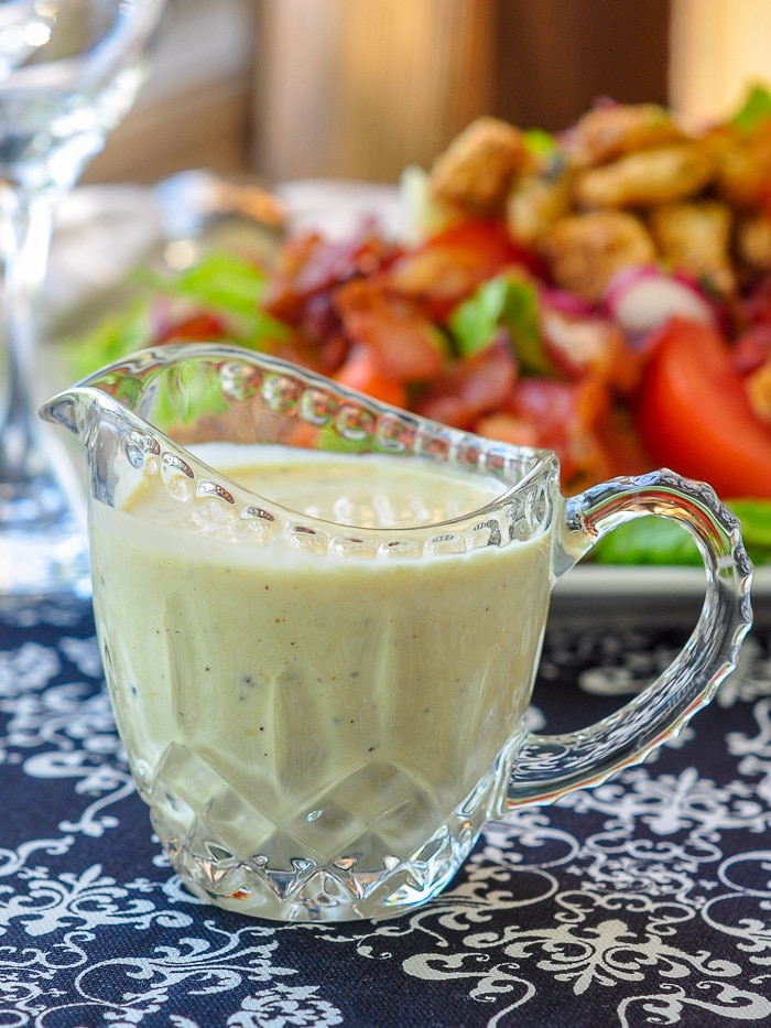 Creamy Dijon Dressing in a small glass jug with BLT salad in the background.
