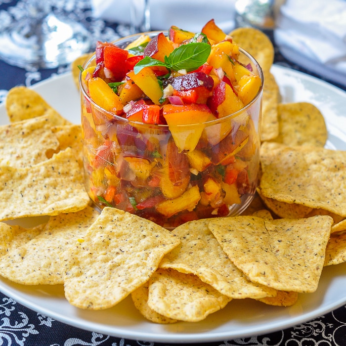 Peach Basil Salsa in a clear class serving dish with tortilla chips