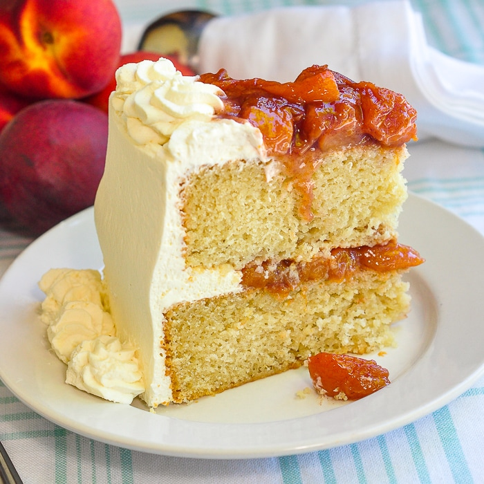 Roasted Peaches and Cream Cake photo of a singe slice on a white plate with fresh peaches in the background