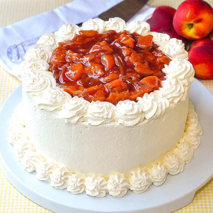 Roasted Peaches and Cream Cake photo of uncut cake on a white serving plate