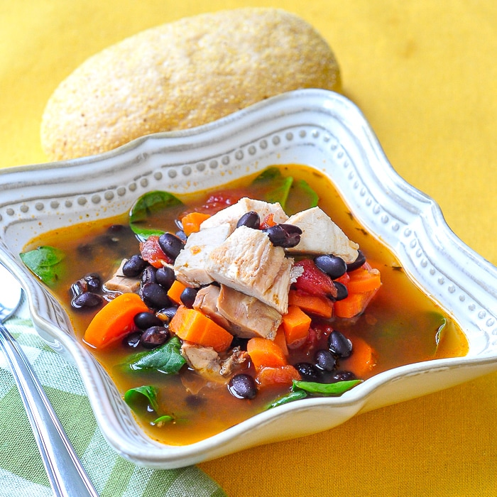 Barbecue Chicken Soup with black beans in a square bowl with roll on the side
