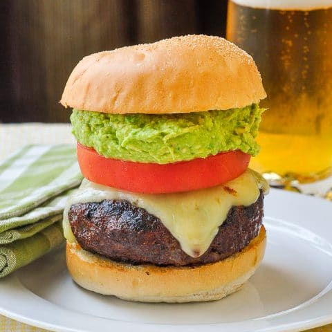 Chorizo Pepper Jack Cheeseburgers with Guacamole photo of a single completed burger with a glass of beer in the background