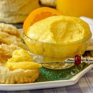 Maple Orange Butter close up photo of a pot of butter being spread on a biscuit