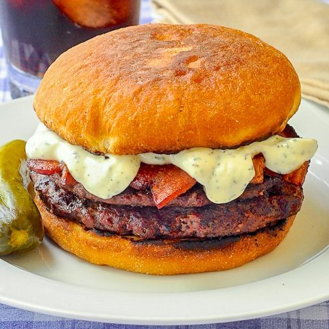 The Ultimate Newfie Touton Burger close up photo of burger on white plate with a dill pickle
