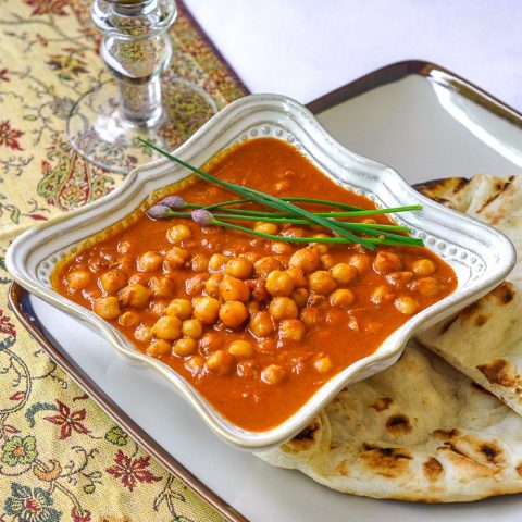 Easy Coconut Chick Pea Korma single serving in a white bowl with naan on the side