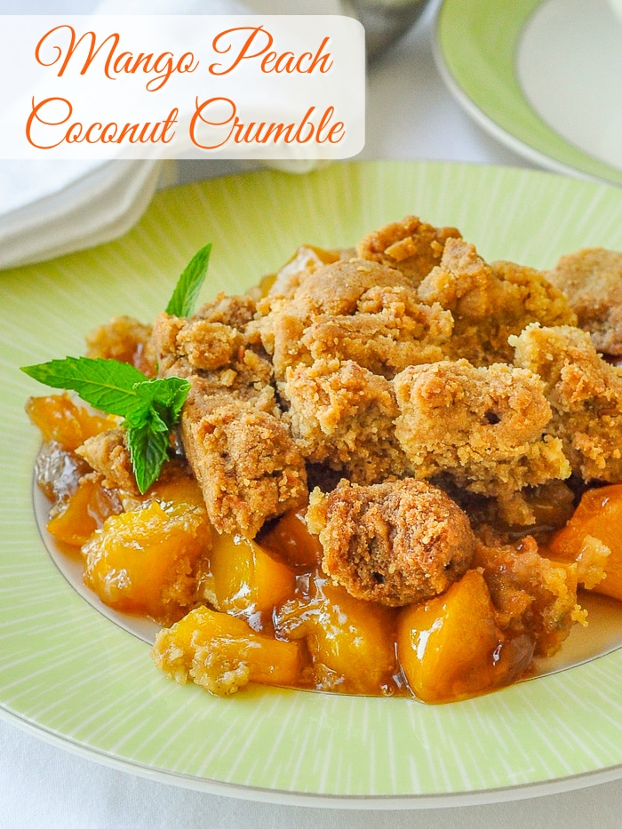 Mango Peach Coconut Crumble is an incredible combination of tropical and local flavours that combine to make one fantastic comfort food dessert. A scoop of good vanilla or coconut ice cream makes it even better. #tropicaldesserts #mangodesserts #peachdesserts #dinnerpartydessert