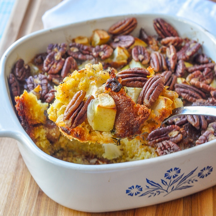 Apple Pecan Cornbread Stuffing close up photo of stuffing being served from a white Corningware casserole dish