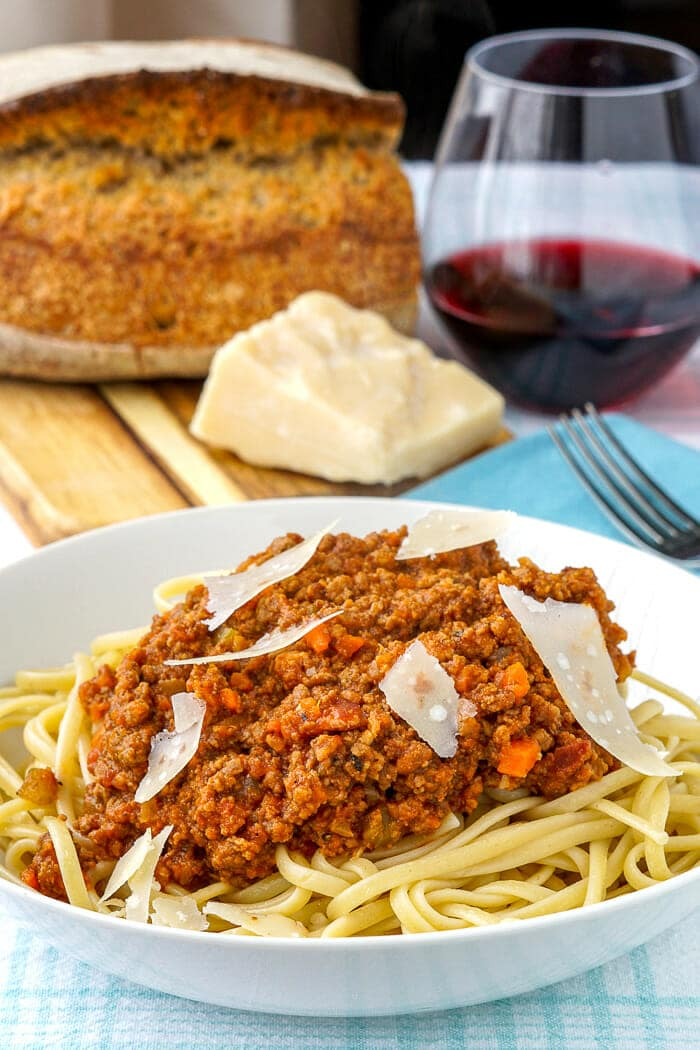 The Best Bolognese Sauce photo with artisan bread and a glass of red wine