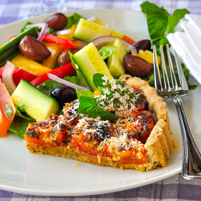Photo of one slice of tomato parmesan tart with side salad on a white plate